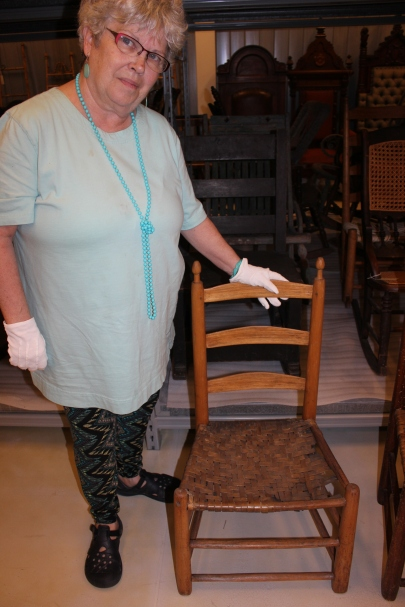 Ellen (Wagner) Hadden at the Waterloo Region Museum with a chair made by her 3X great grandfather Jacob Hailer in 1847